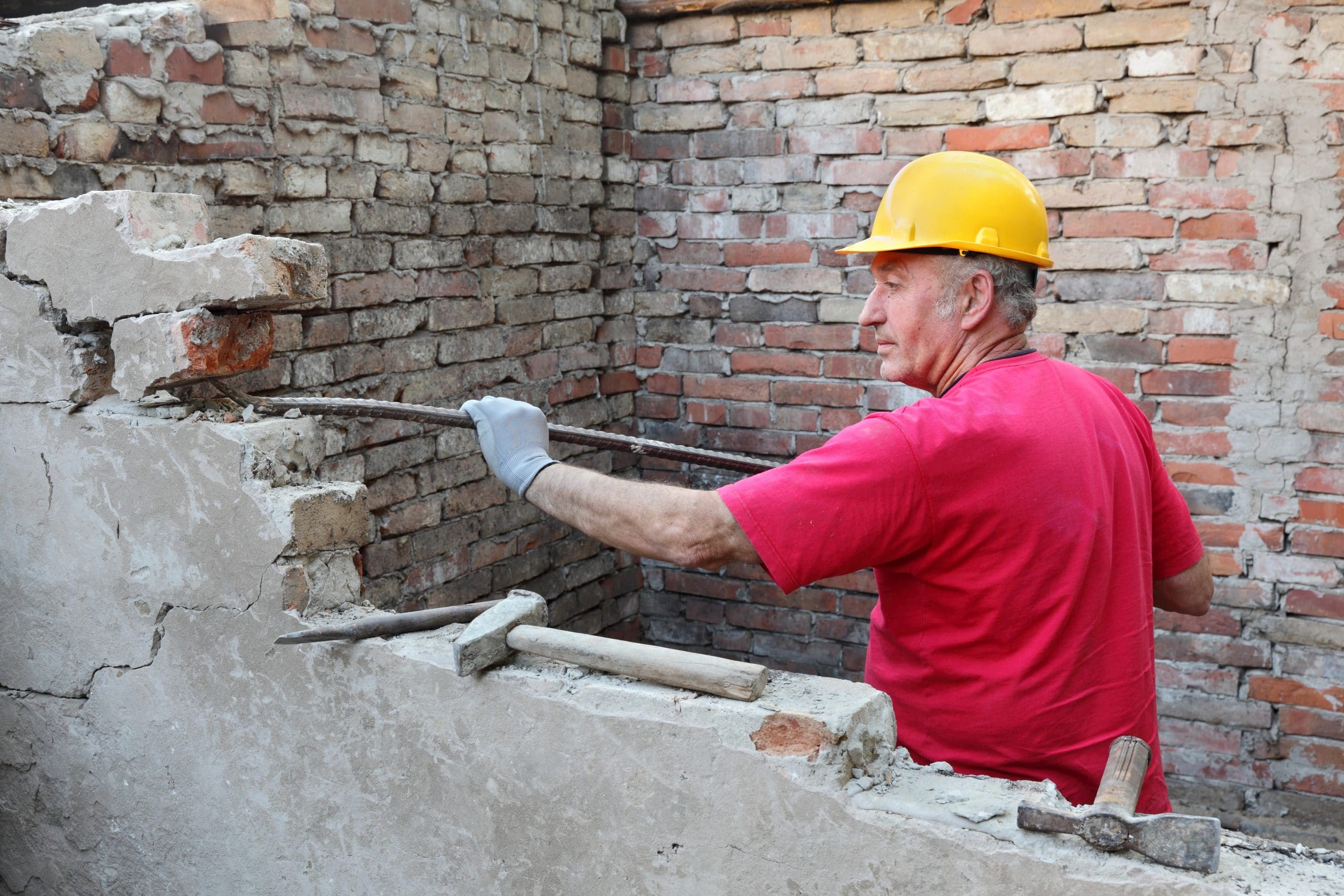 Workman manually demolishing wall to reclaim the bricks