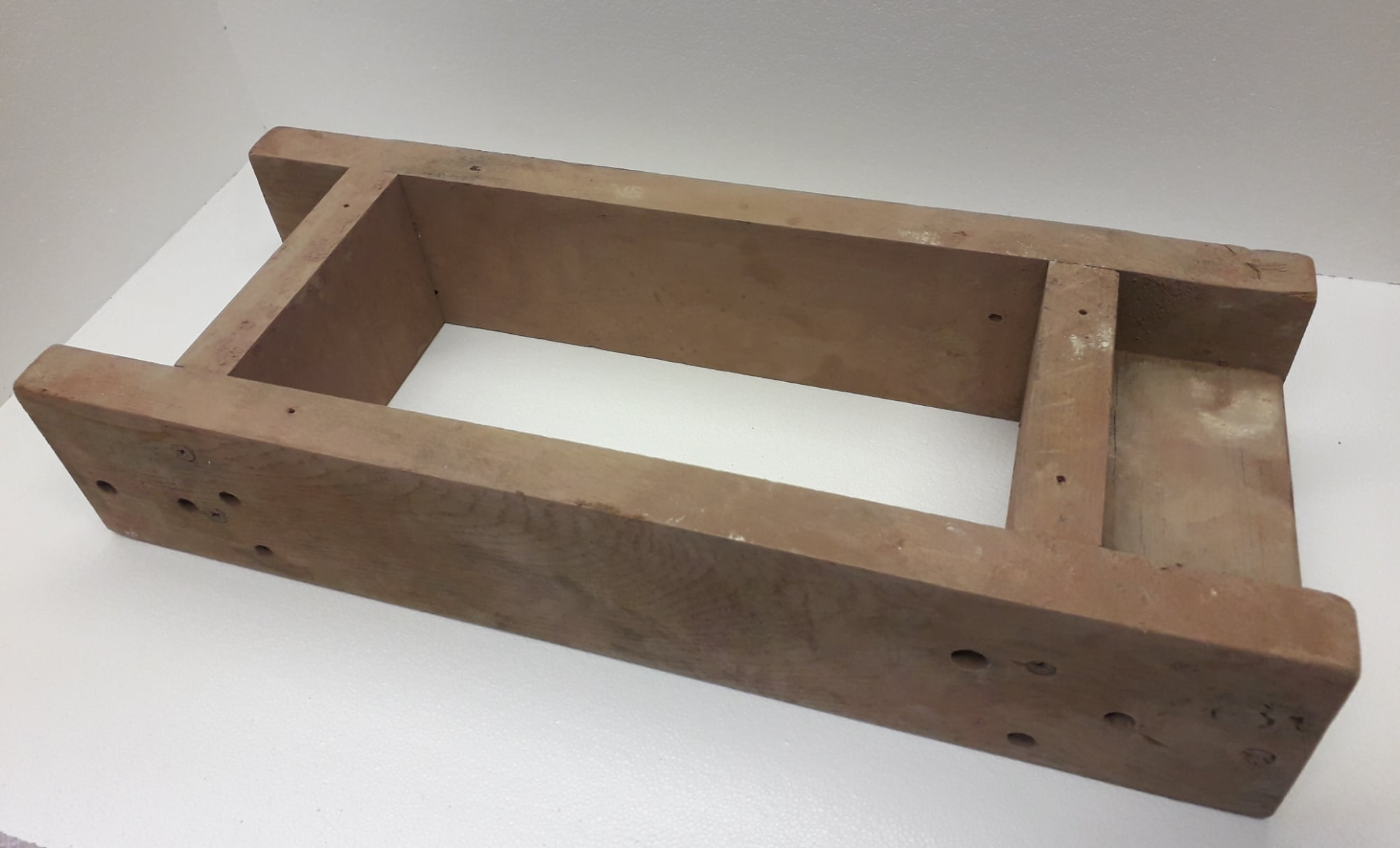 A wooden open bottomed brick mould for handmaking bricks