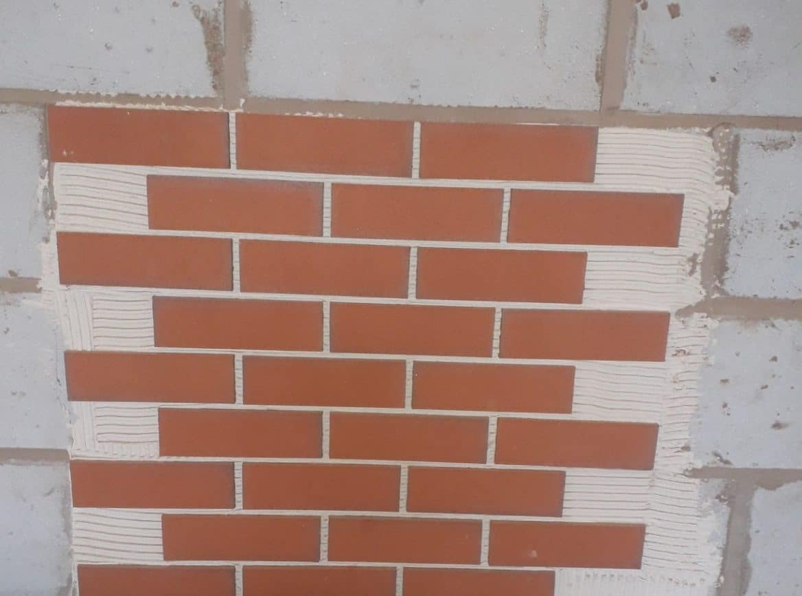 Brick slips stuck on a lightweight concrete block wall using cement based brick slip adhesives