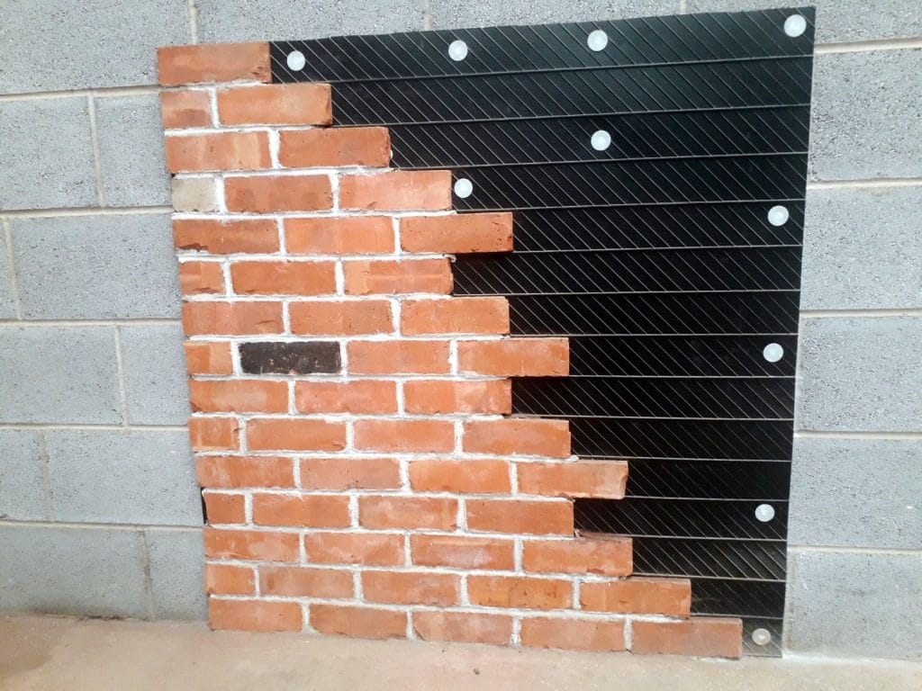 Brick Slips bonded to a plastic tracking sheet with epoxy brick slip adhesives on a block wall